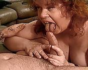 Mature redhead pumping a huge cock in her plump pussy.